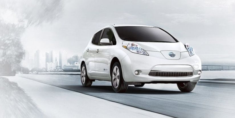 An overexposed image of a white 2017 Nissan Leaf driving away from a city