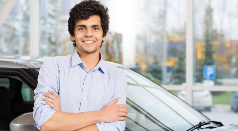A young man leaning on a car and smiling about his Car buying experience