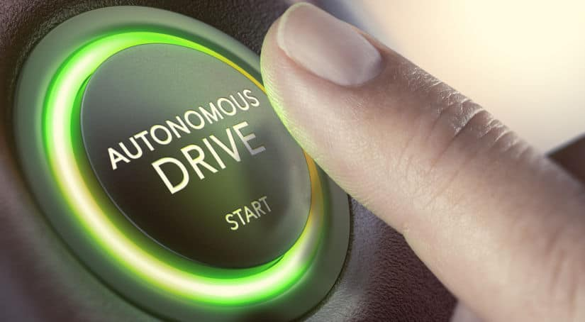 """Finger hovering over a circular black button with glowing green edges that says """"Autonomous Drive START"""""""