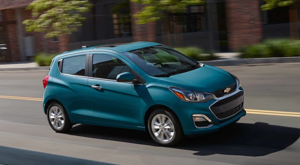 Teal 2019 Chevy Spark driving on city street
