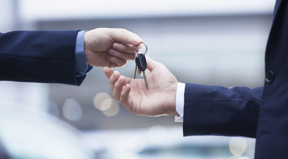 One hand holding car keys to another