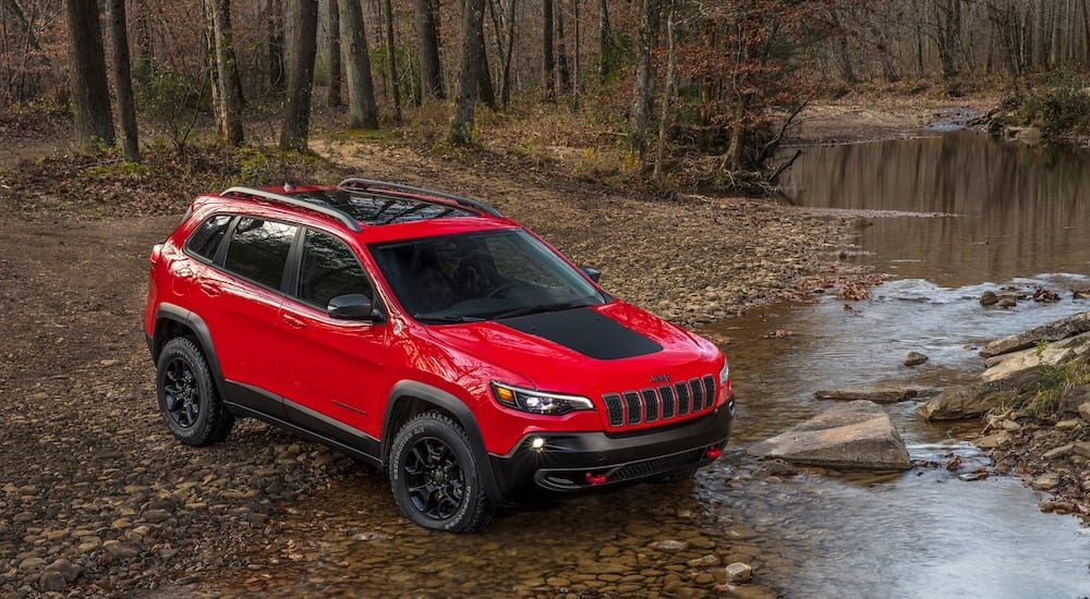 A red 2019 Jeep Cherokee navigates a river crossing