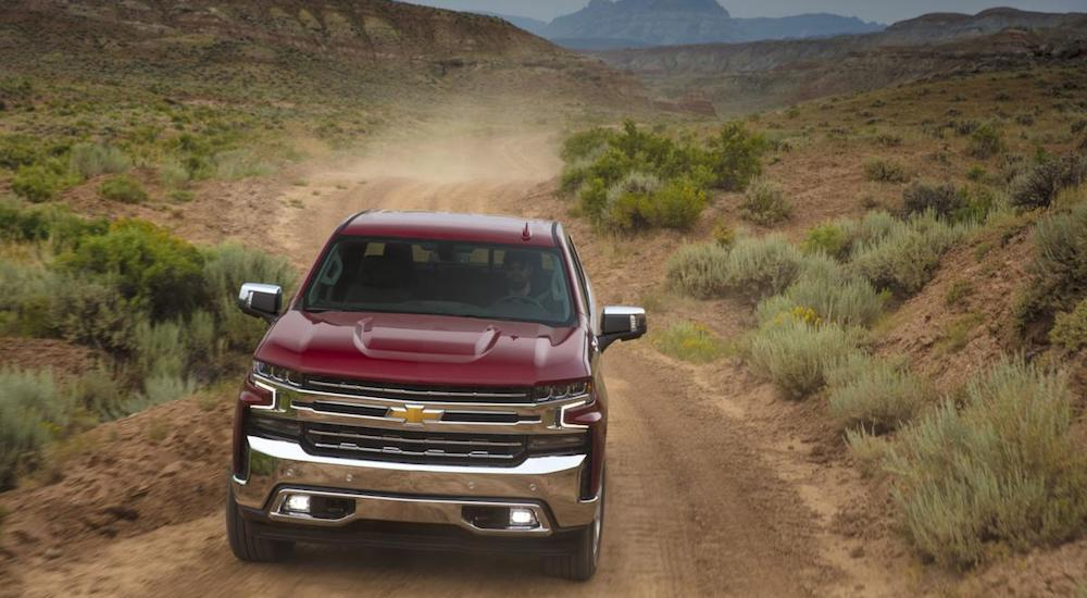 A red 2019 Chevy truck for sale travels a dusty dirt road in a desert