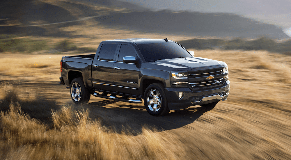 A black 2019 Chevy Silverado driving in a field