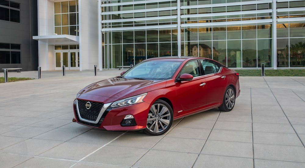 A red 2019 Nissan Altima in front of a glass building