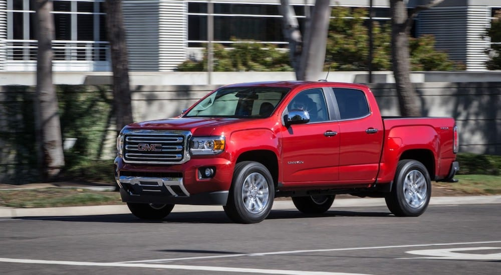 A red 2019 GMC Canyon driving away from a GMC Dealer Near Me