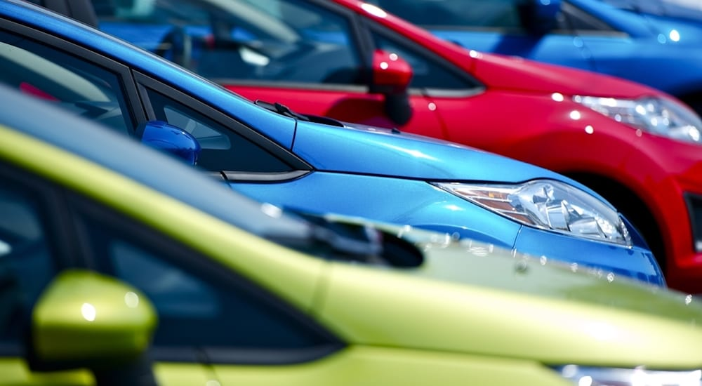A closeup image of blue, green, and red cars.