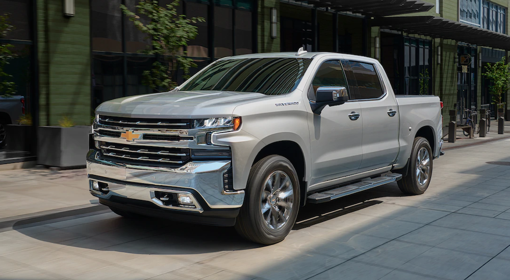 A silver 2019 Chevy Silverado 1500 is parked in front of a building. Check out power when comparing the 2019 Chevy Silverado vs 2019 Toyota Tundra.