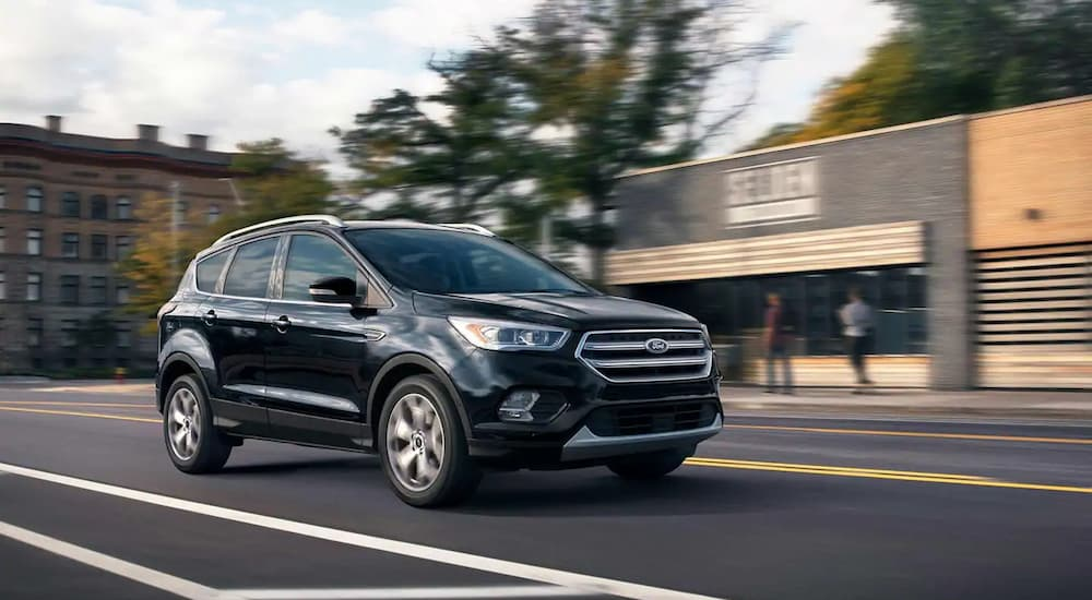 A black 2019 Ford Escape Titanium is driving downtown. Check out trim levels when comparing the 2019 Ford Escape VS 2019 Nissan Rogue.