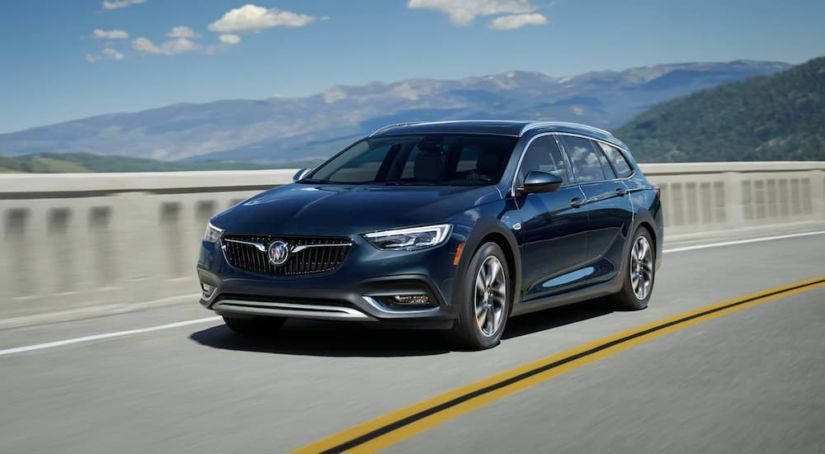 a dark colored 2019 Buick Regal Tourx is driving up high with mountain views. It is part the Buick SUVs and crossovers.