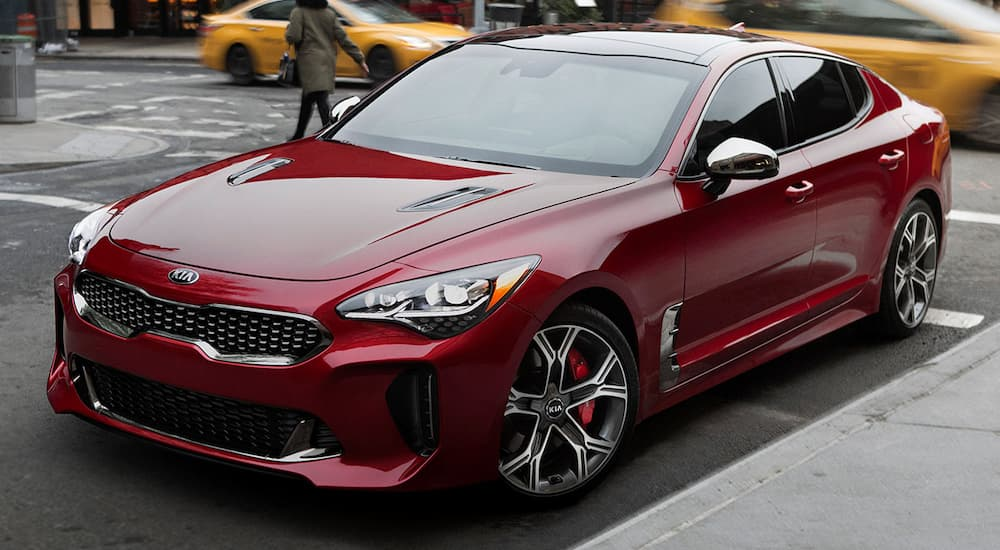 A dark red 2019 Kia Stinger is parked in a city with taxis behind it. If you want to check one out search for 'KIA dealership near me'.