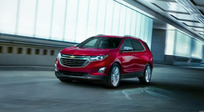 A red 2019 Chevy Equinox is driving past a lit building at night.
