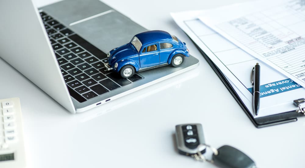 A blue toy car is on a laptop next to car keys.