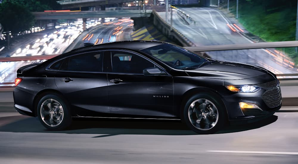 A black 2019 Chevy Malibu is driving on an overpass over a highway at night.