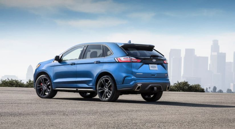 A blue 2019 Ford Edge ST is in front of a city skyline.