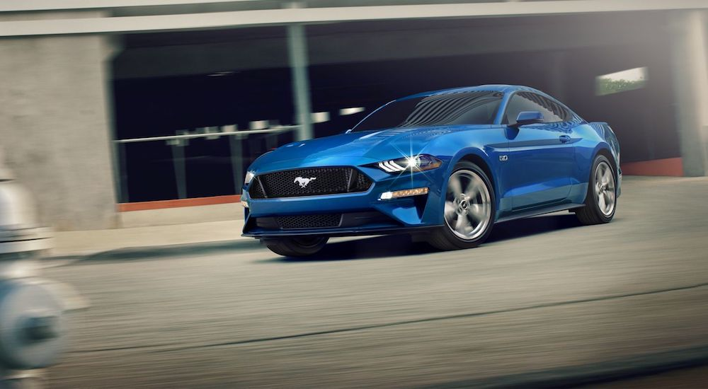 A blue 2020 Ford Mustang is driving on a city street on a sunny day.