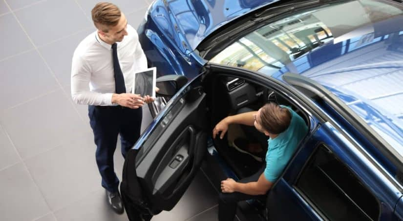 A sales person is talking to a buyer sitting in a blue car.