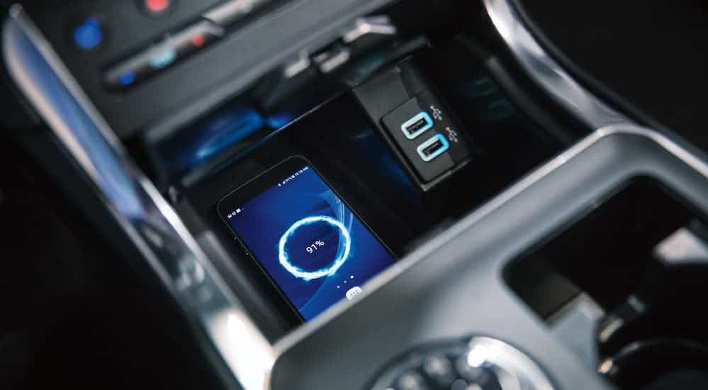 A phone on a wireless charging port in the 2019 Ford Edge is being charged.