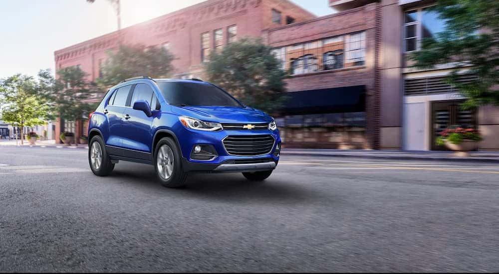A blue 2017 Chevy Trax, which is a reliable used vehicle you could buy for your New Year's Resolution, is driving on a city street.