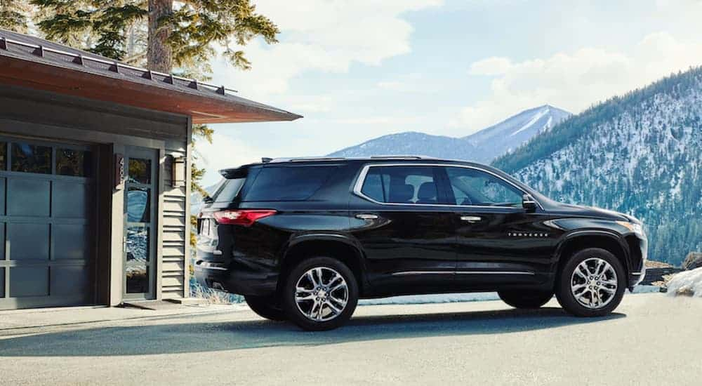A black 2020 Chevy Traverse is parked outside of a home with mountain views.