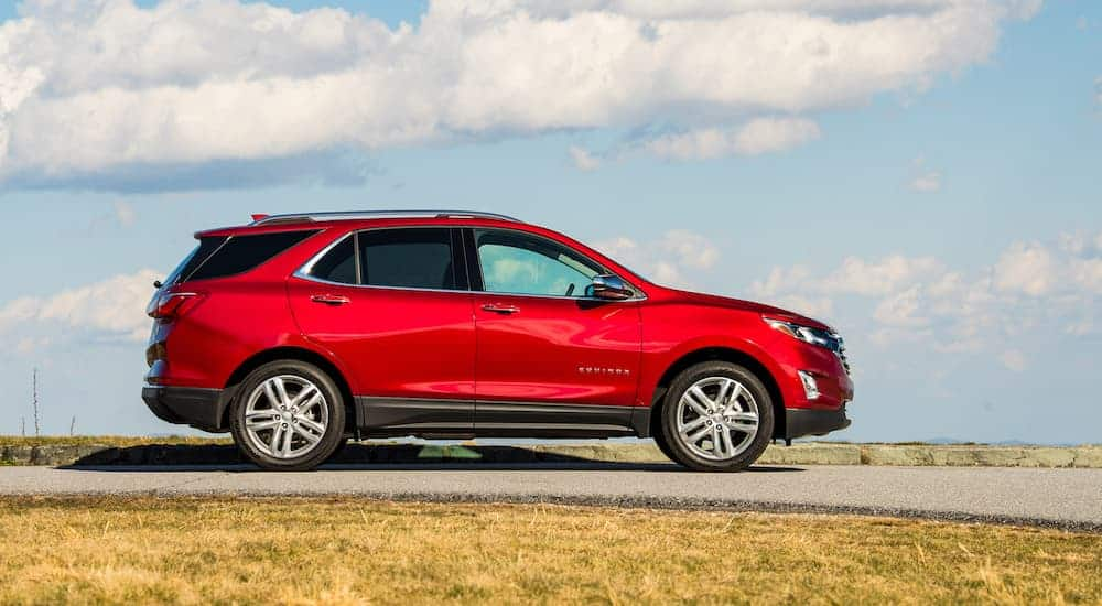 A red 2020 Chevy Equinox is shown from the side on a blue cloudy day.