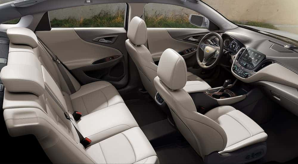 A birds eye view of the grey leather interior of a 2020 Chevy Malibu with an infotainment system is shown.