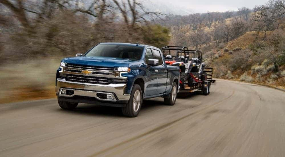 A blue 2020 Chevy Silverado 1500 is towing side-by-sides on a trailer uphill.