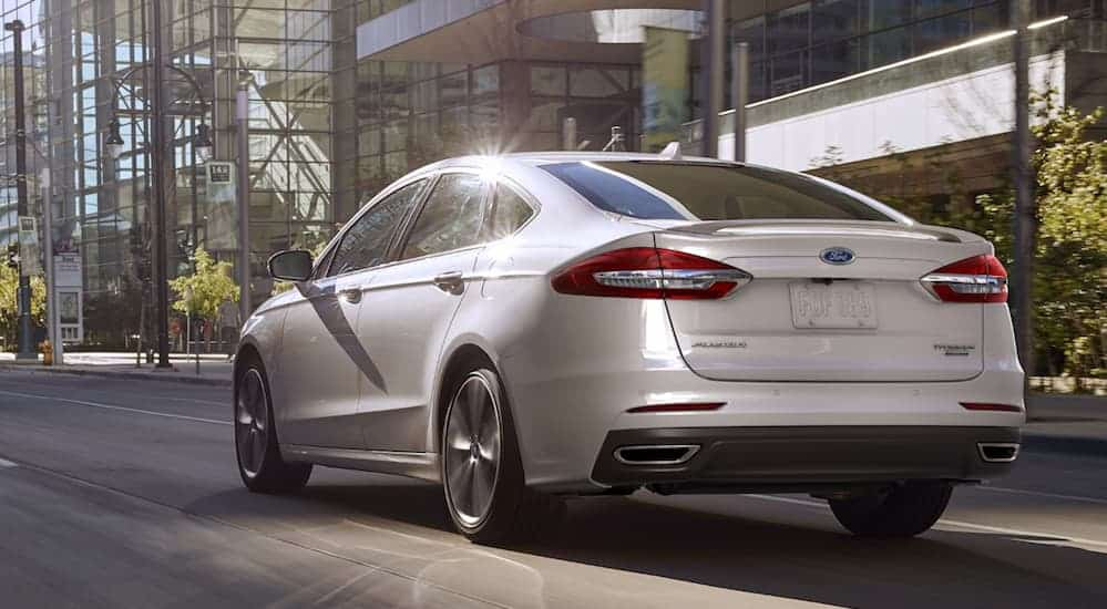 A white 2020 Ford Fusion is shown from the rear driving on a city street passed glass buildings.