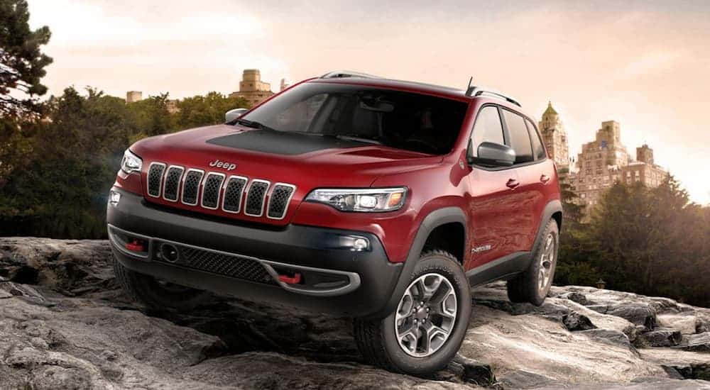 A red 2020 Jeep Cherokee Trailhawk is driving on a large rock through the woods.