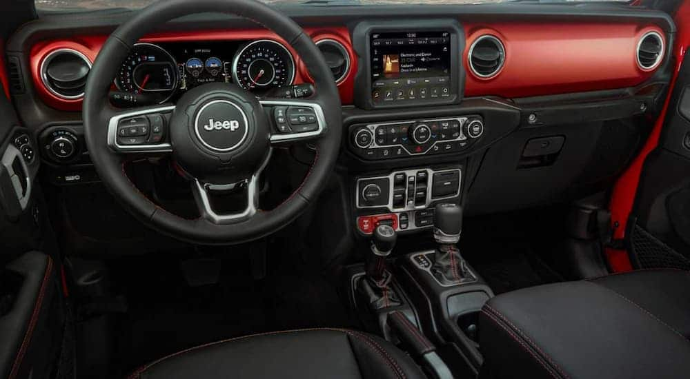 The black and red interior of a 2020 Jeep Gladiator is shown with an infotainment system.