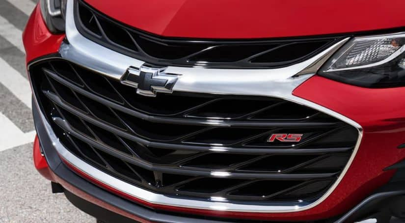 A close up view of the Chevy logo on a red Chevy Sonic is shown.