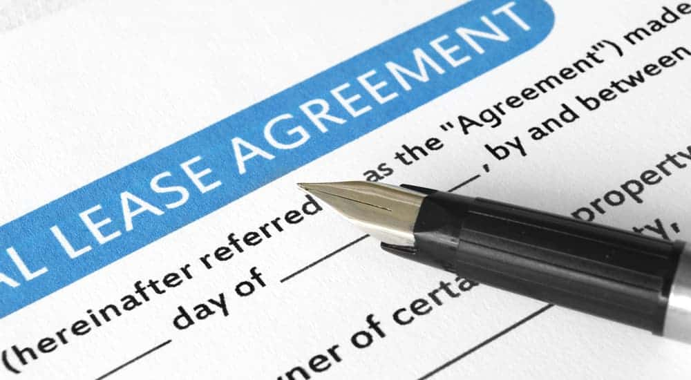 A pen is on a paper that says 'lease agreement.'