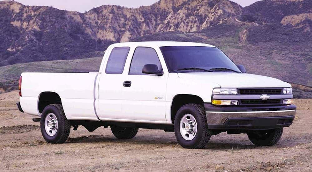 A white 1999 used Chevy Silverado 1500 is parked on a dirt trail with mountains in the distance.