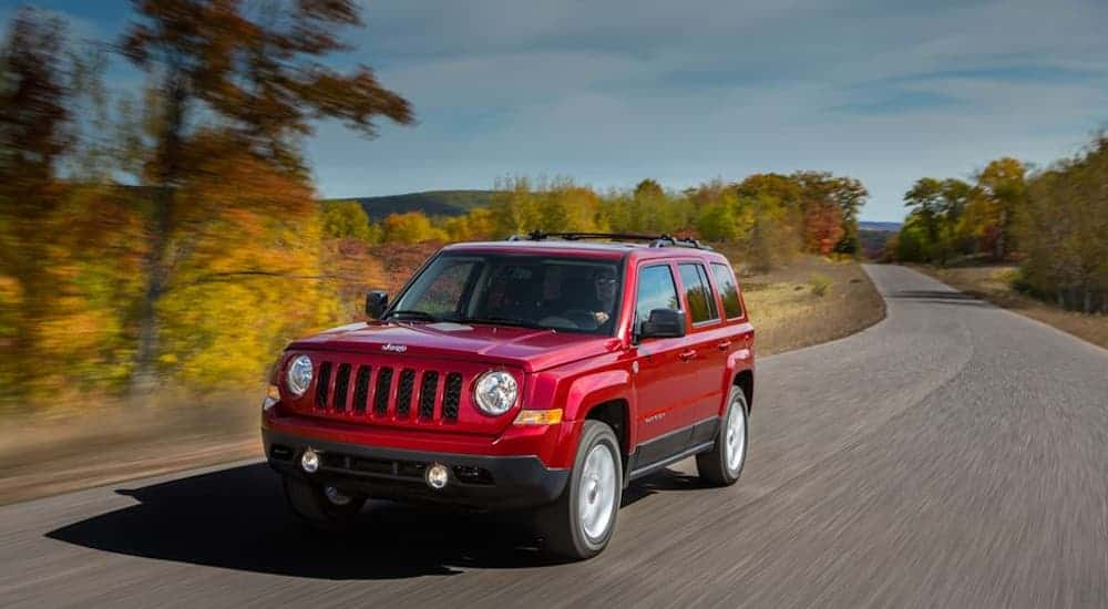 A red 2016 Jeep Patriot, which is a popular option among used cars for sale, is driving on a rural road in fall