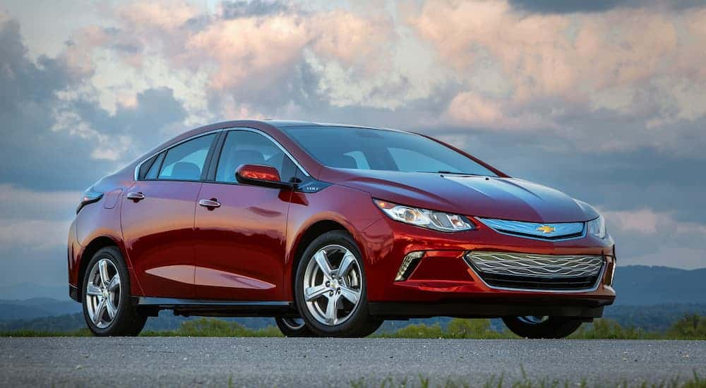 A red 2019 Chevy Volt is parked in an empty parking lot at dusk.