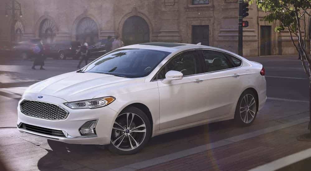 A white 2020 Ford Fusion, a popular Ford car at a Ford dealership near me, is parked on a city street.