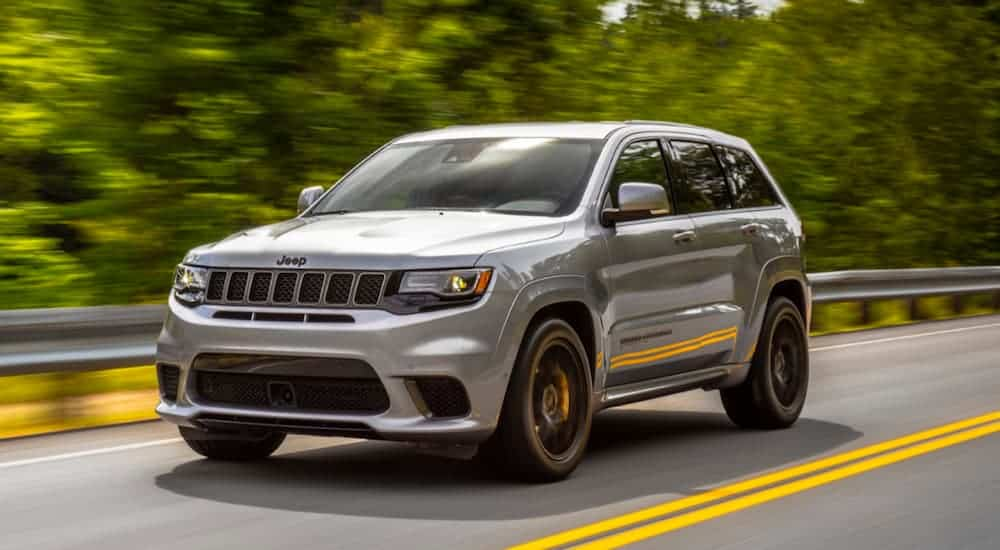 A grey 2020 Jeep Grand Cherokee Trackhawk, which is a popular Jeep for sale, is driving on a treelined road.