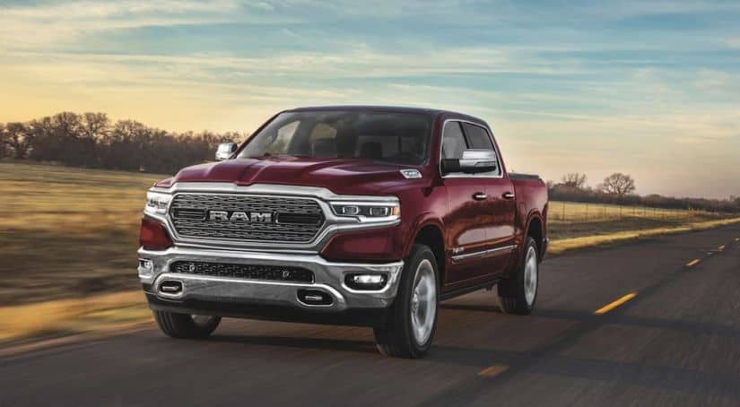 A red 2020 Ram 1500, which is popular among Ram trucks, is driving on a highway before sundown.