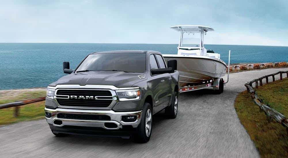 A grey 2020 Ram 1500 is towing a boat past the ocean.