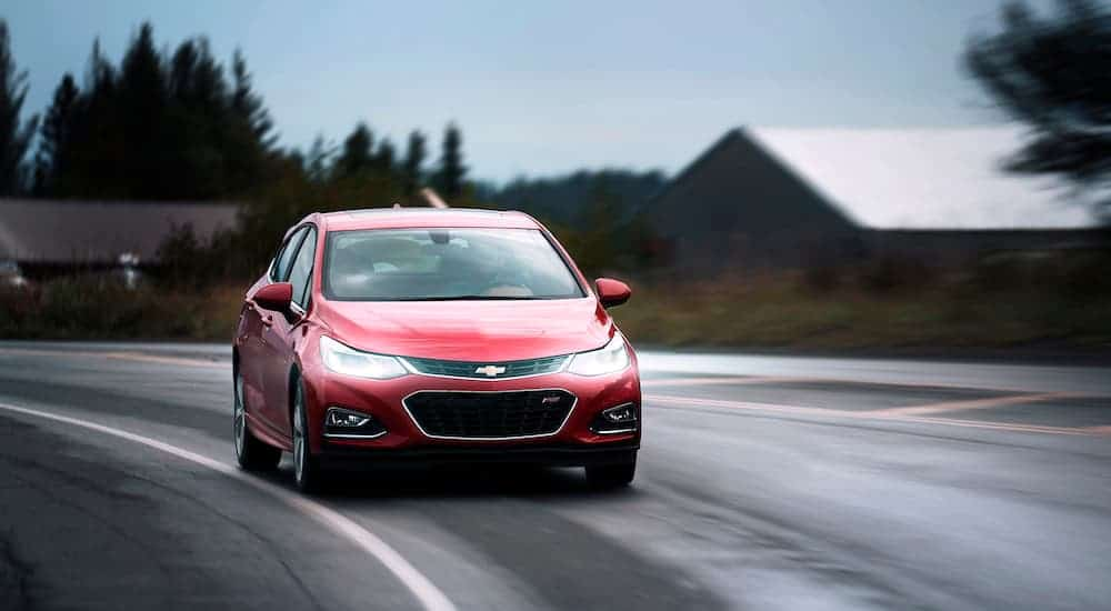 A red 2018 used Chevy Cruze is driving around a corner on a wet road.