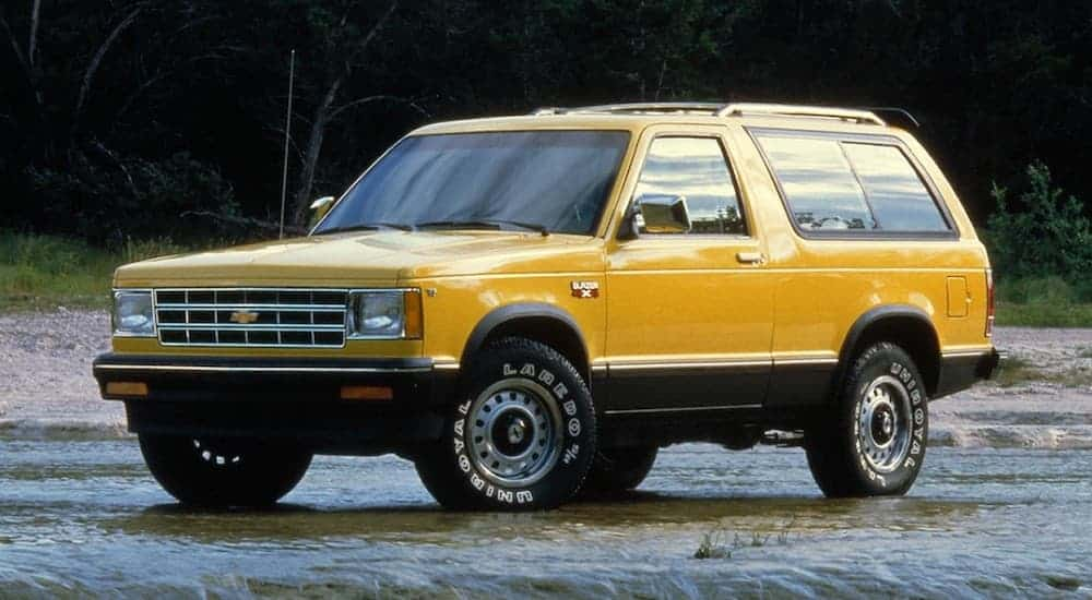 A yellow 1983 Chevy S10 Blazer is parked in front of dark trees.