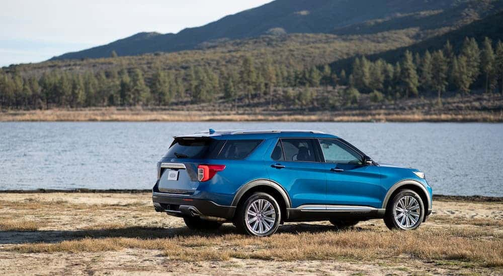 A blue 2020 Ford Explorer Hybrid is parked next to a lake.