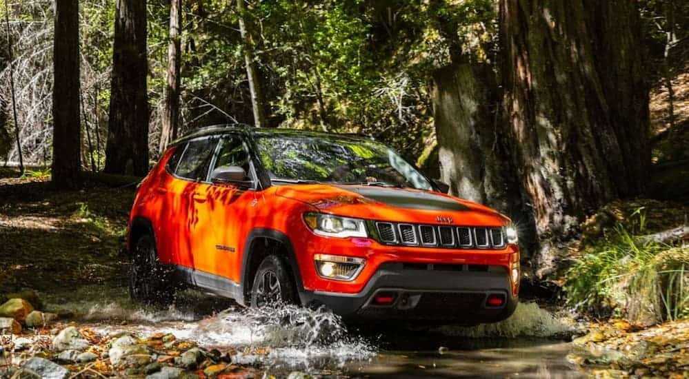 A red 2020 Jeep Compass Trailhawk is driving through the woods on a dirt trail.