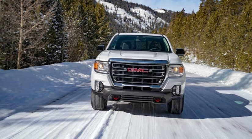 A white 2021 GMC Canyon AT4 is driving forward on a snow covered road.