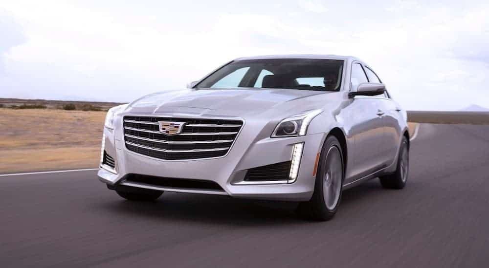 A silver 2018 Cadillac CTS, which is popular among Cadillac's used cars, is driving on an empty highway.