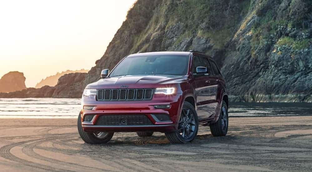 A red 2020 Jeep Grand Cherokee is parked on a beach.