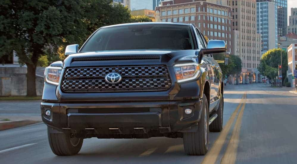 A black 2020 Toyota Tundra is driving on a city street with city buildings in the distance.