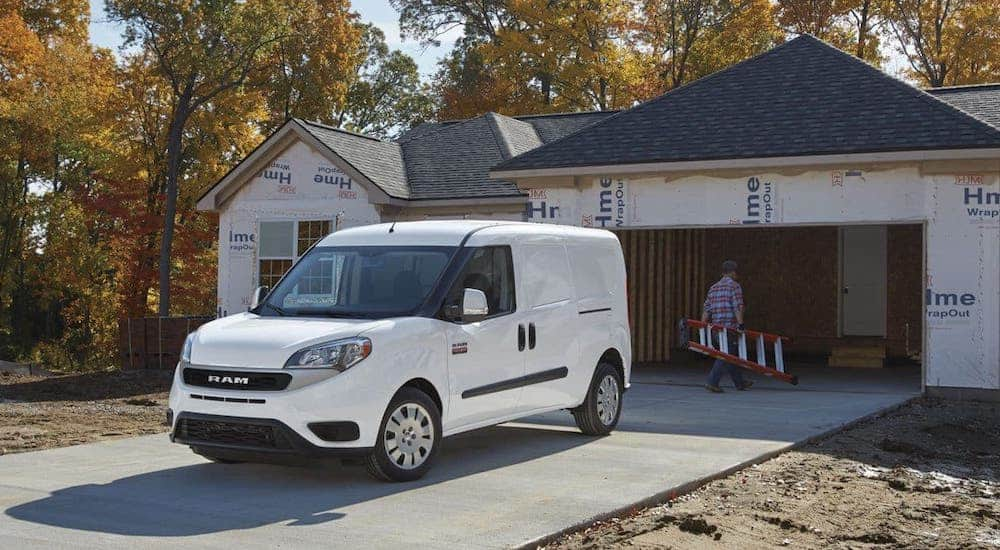 A man carrying a ladder is walking away from an unmarked white 2020 Ram ProMaster van towards a house that is under construction.
