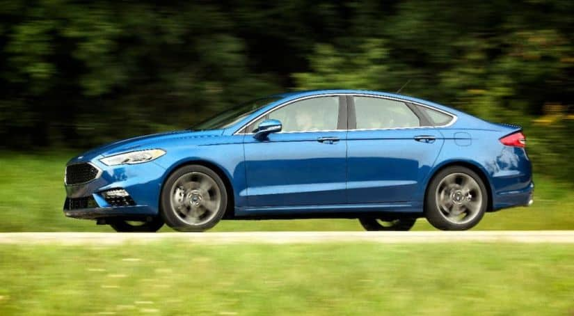 A blue 2017 Ford Fusion Sport is driving on a rural road away from a Used Car Dealerships Near Me.