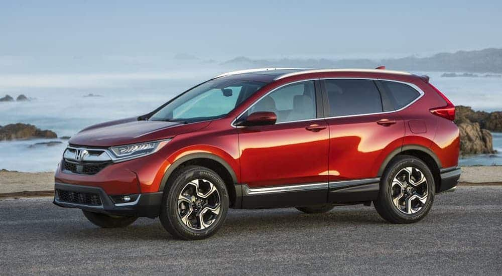 A red 2017 Honda CR-V is parked in front of a beach.